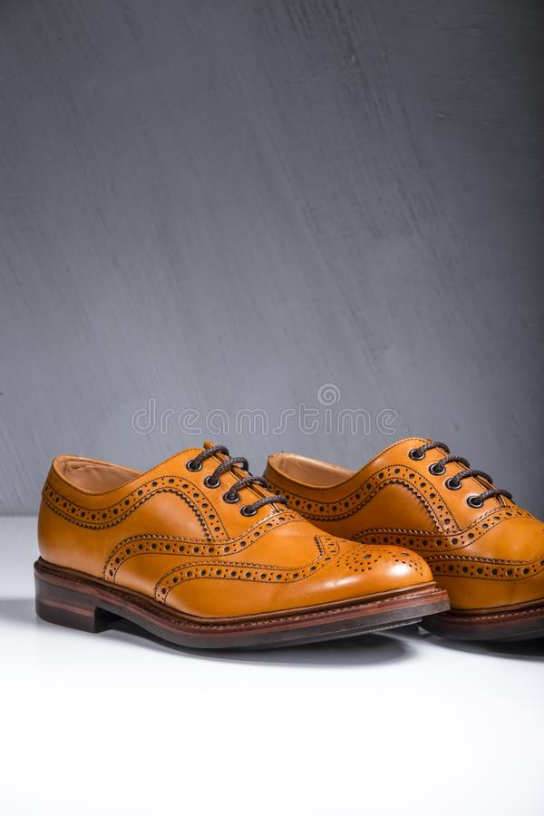 Pair of Luxury Male Full Broggued Tan Leather Oxfords. Closeup of Pair of Luxury Male Full Broggued Tan Leather Oxfords Shoes On White Surface. Against Gray Wall stock images