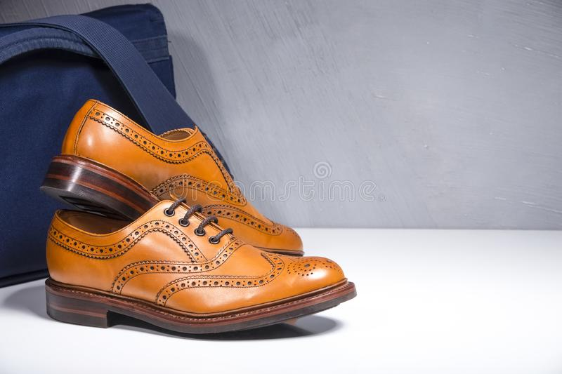 Pair of Luxury Male Tanned Full Broggued Oxford Calf Leather Shoes Along Messenger Blue Bag on White Surface. Horizontal Image stock image