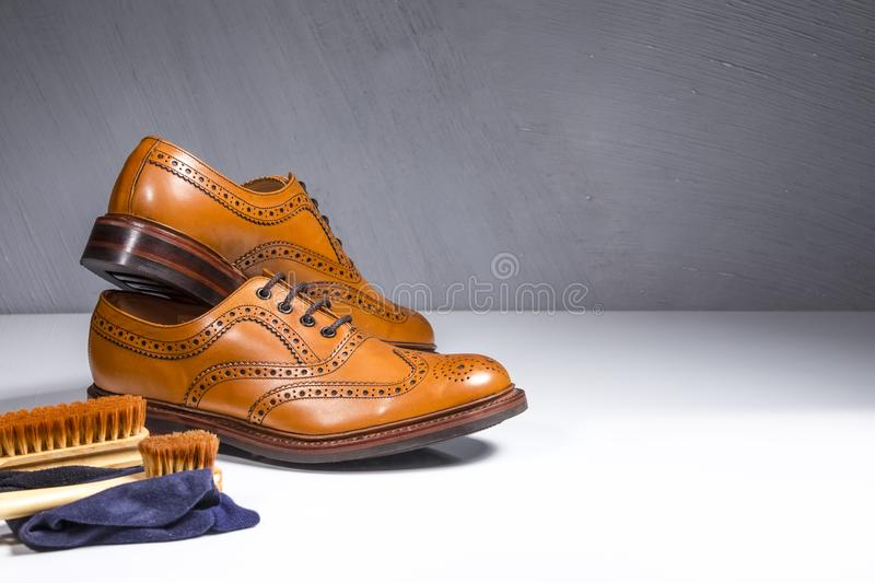 Pair of Luxury Male Tanned Full Broggued Oxford Calf Leather Shoes Along with Cleaning Accessories and Cloth. Horizontal Image royalty free stock images