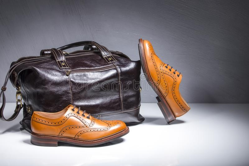 Pair of Luxury Male Tanned Full Broggued Oxford Calf Leather Shoes Along With Dakr Brown Leather Travel Bag on White Surface. Horizontal Composition royalty free stock image