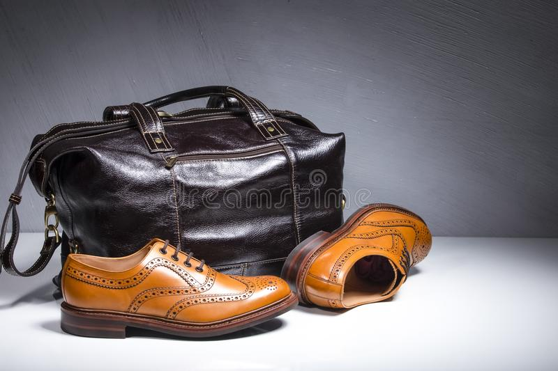 Pair of Luxury Male Tanned Full Broggued Oxford Calf Leather Shoes Along With Dakr Brown Leather Travel Bag on White Surface. Horizontal Image stock photography