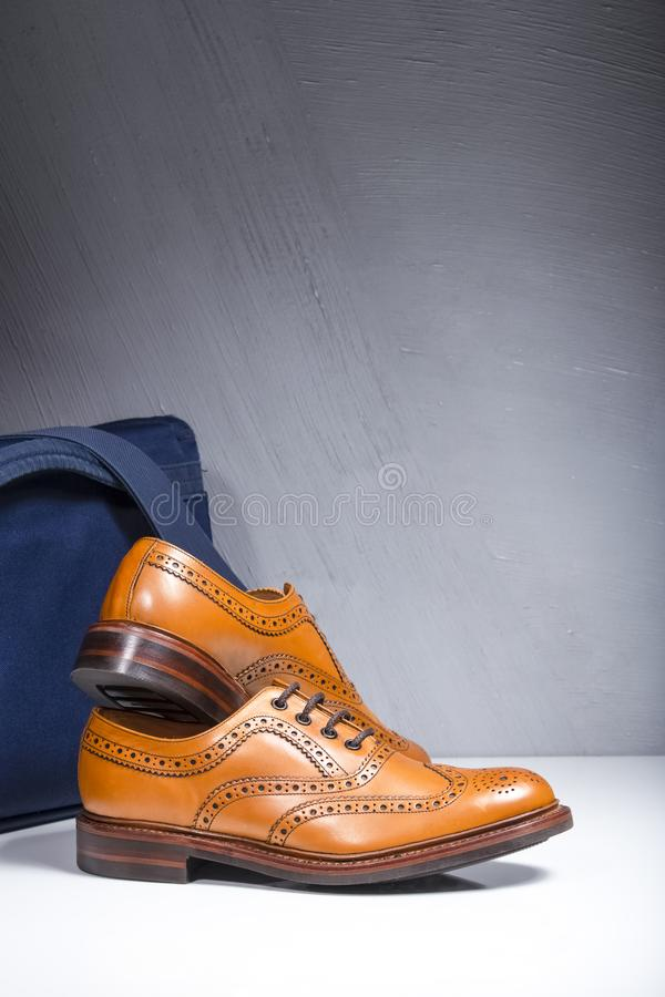 Pair of Luxury Male Tanned Full Broggued Oxford Calf Leather Shoes Along Messenger Blue Bag on White Surface. Vertical Composition royalty free stock photo