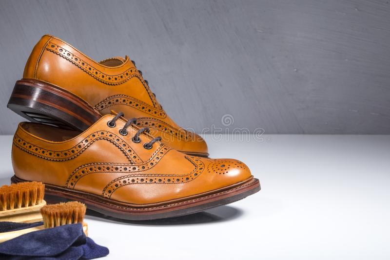 Pair of Luxury Male Tanned Full Broggued Oxford Calf Leather Shoes. Along with Cleaning Accessories and Cloth.Horizontal Image Orientation royalty free stock photos