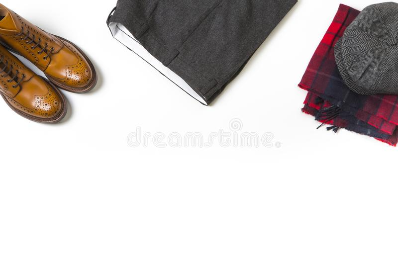 Pair Of Luxury Tan Brogue Boots, Fashion Old School Hat over Checkered Scarf and Gray Herringbone Trousers On White royalty free stock image