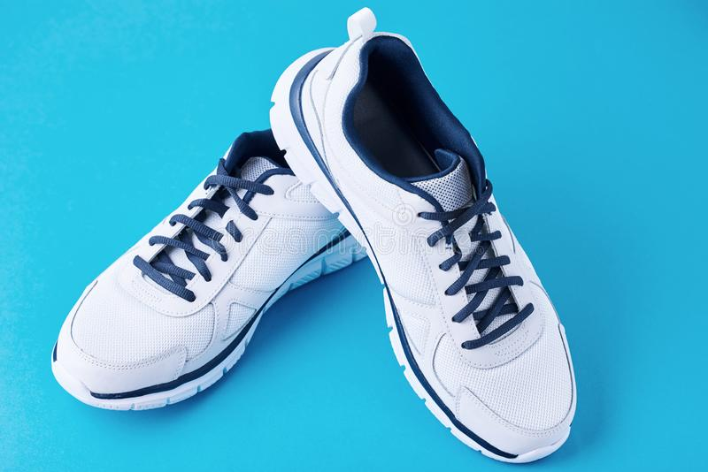 Pair of male white sneakers on a blue background. Sport shoe close up. Pair of male white sneakers on blue background. Sport shoe close up stock images
