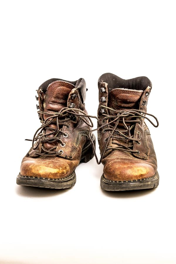 Pair of Men`s Dirty Beat Up Worn Out Brown Leather Work Boots Isolated on White Background royalty free stock photos