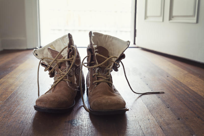 Pair of men's worn leather boots in doorway of home royalty free stock photos