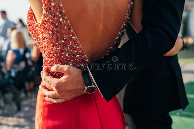 A pair of men and women are well dressed, hugging each other in the open air.  stock images