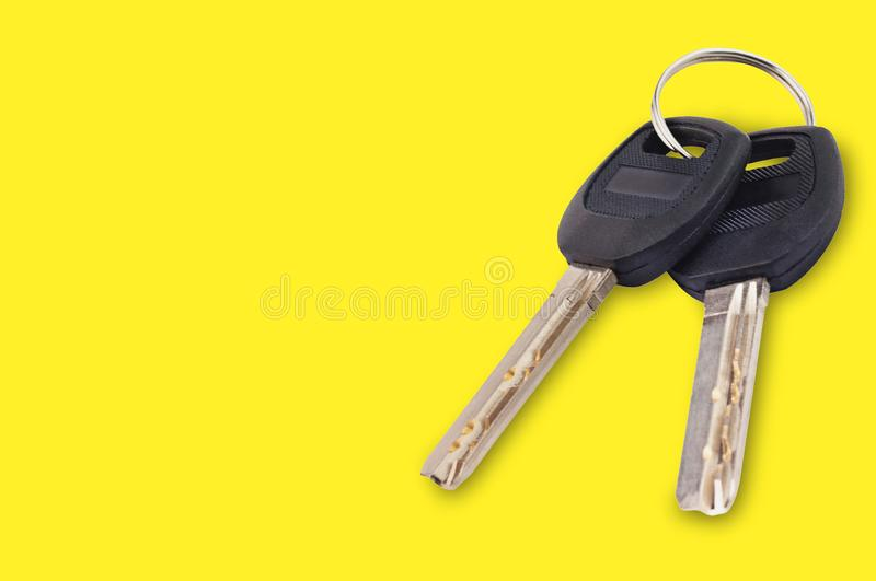 Pair of metal shiny keys with black plastic or rubber handle attached of keyring for door or car on yellow background with copy sp stock images
