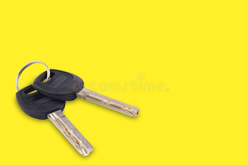 Pair of metal shiny keys with black plastic or rubber handle attached of keyring for door or car on yellow background with copy sp royalty free stock photos