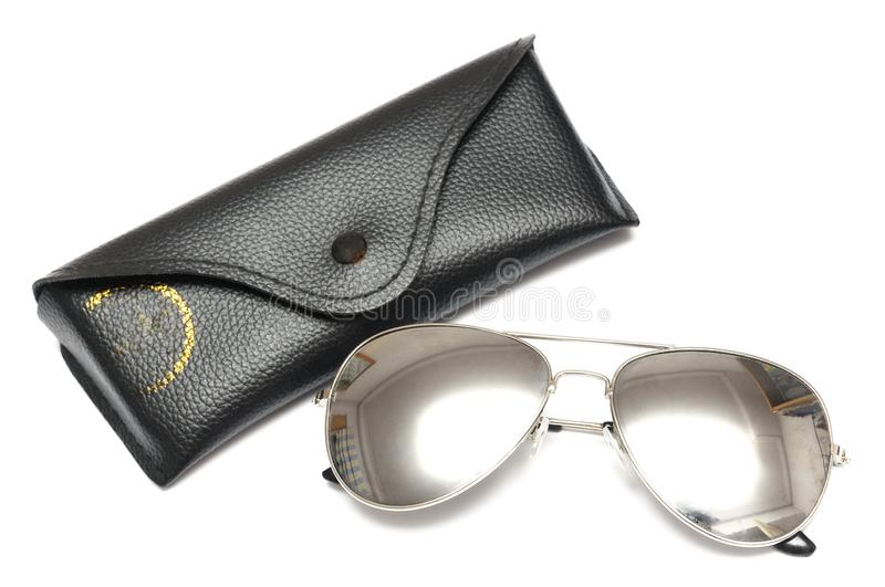 A pair of metallic silver aviators sunglasses with a black holder pouch. A photo taken on a pair of metallic silver aviators sunglasses with a black holder pouch stock image