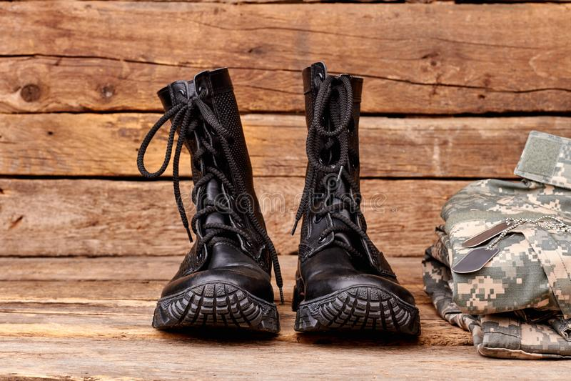 Pair of military boots. Set of soldiers outfit on wood royalty free stock photography