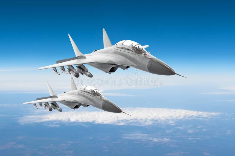 Pair of military fighters jet aircraft on a combat mission, flying high in the sky. royalty free stock photography