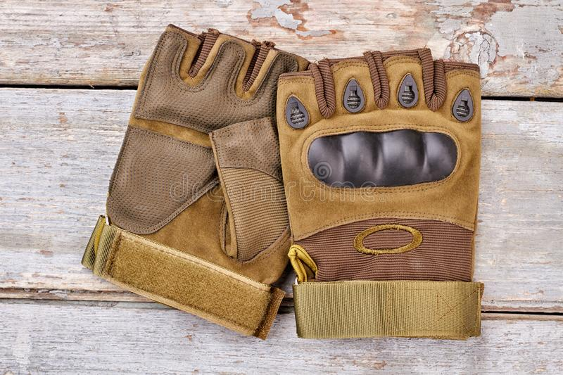 Pair of military fingerless gloves for riding. Wooden desk background. Top view, flat lay stock photography