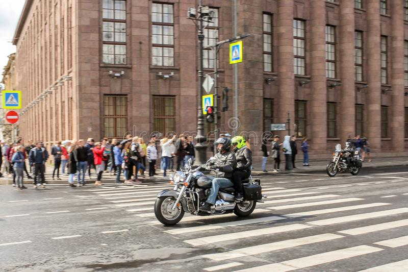 A pair of motorcyclists pass by spectators stock photography