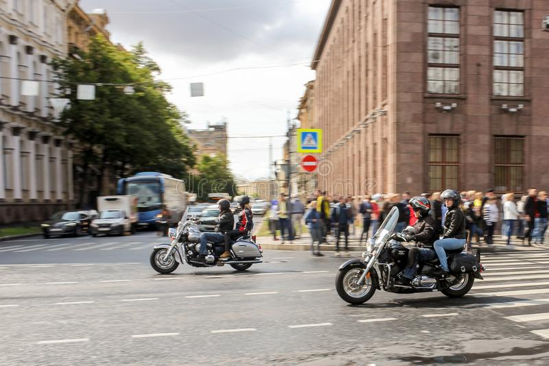 A pair of motorcyclists pass by spectators stock images