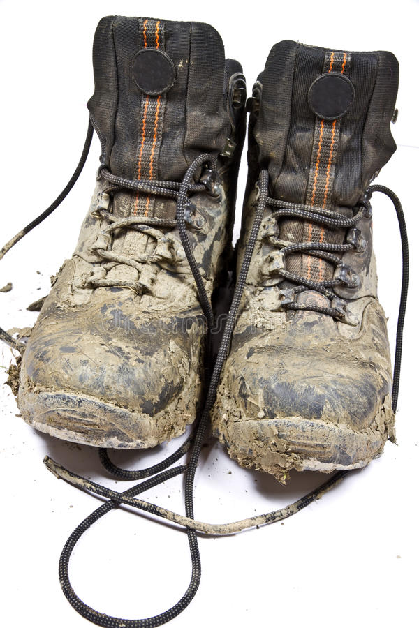 Pair muddy walking boots. Pair of muddy , worn walking or hiking boots on a plain background royalty free stock image