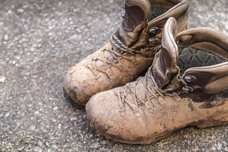 Muddy walking boots. A pair of muddy walking boots with copy space one left side royalty free stock image