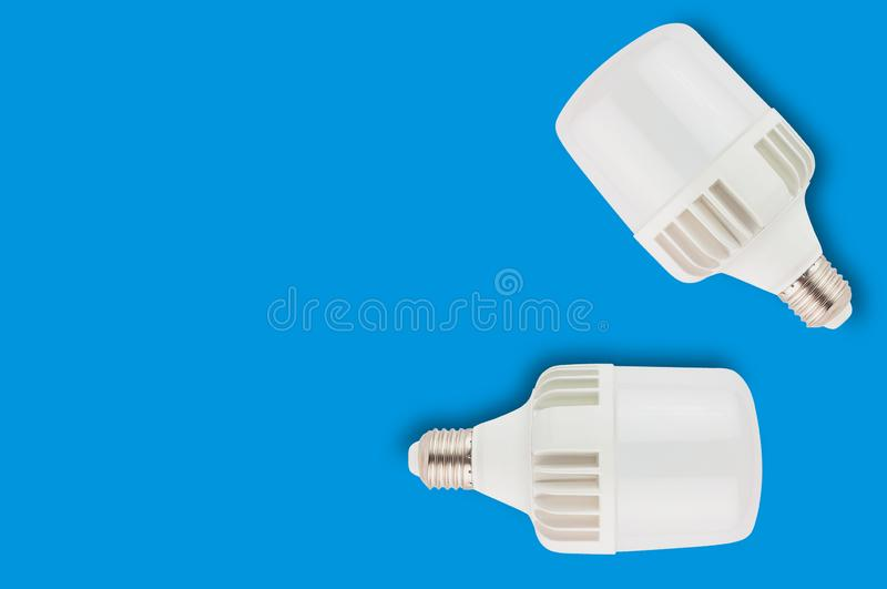 Pair of new plastic led bulbs on blue background with copy space. Saving and economy or green energy concept royalty free stock photo