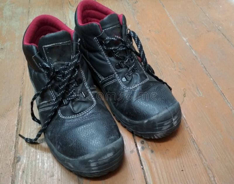 Pair of Old Black Used Dirty Work Boots sur parquet Des chaussures de travail protectrices contre les accidents à l'usine, photos stock