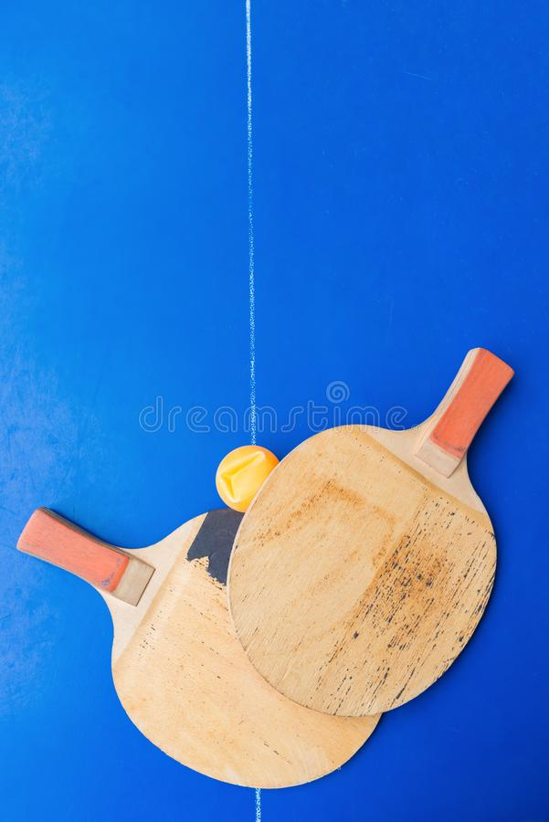Pair of old pingpong rackets and a dented ball on blue pingpong table. Pair of old pingpong rackets and a dented ball on a blue pingpong table stock photos