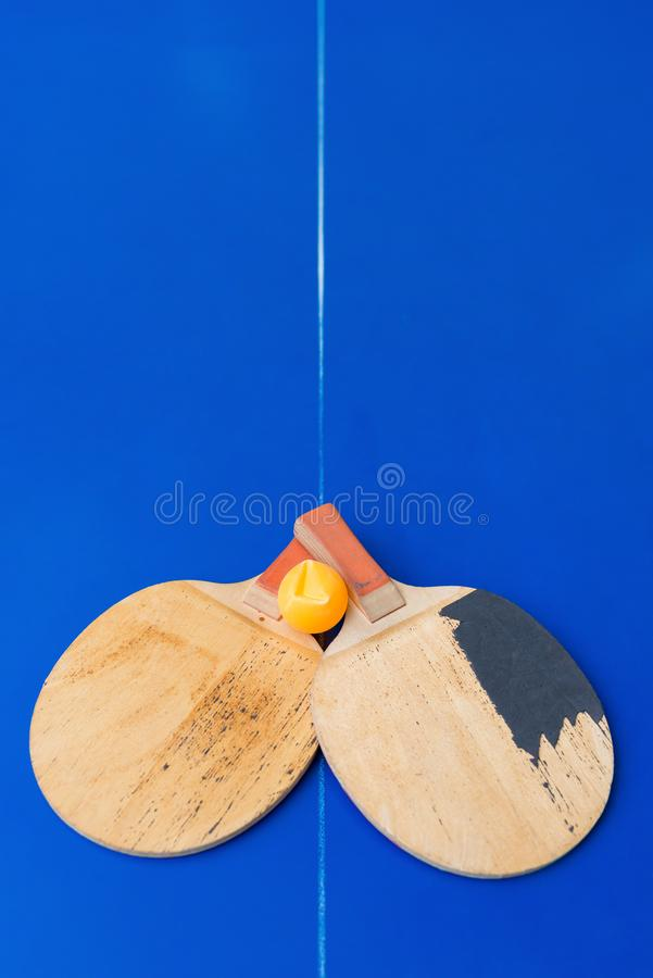 Pair of old pingpong rackets and a dented ball on blue pingpong table. Pair of old pingpong rackets and a dented ball on a blue pingpong table stock photography