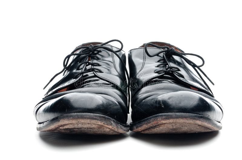 A pair of old worn black leather business shoes. On a white background royalty free stock photos