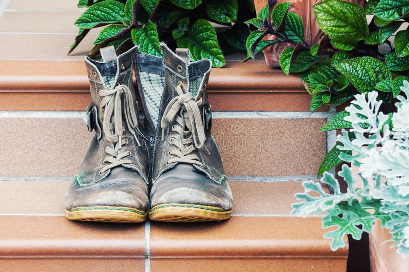 Pair of old worn boots at doorstep royalty free stock image
