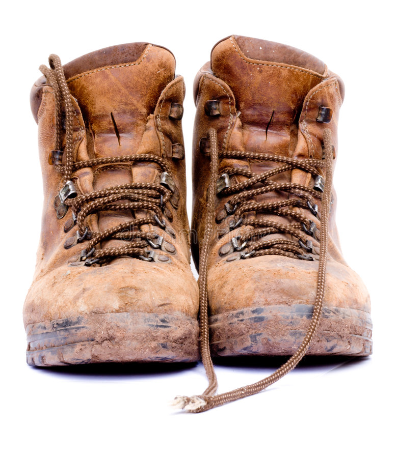 Pair of old worn walking boots. A pair of old worn walking boots isolated on a white background royalty free stock photography
