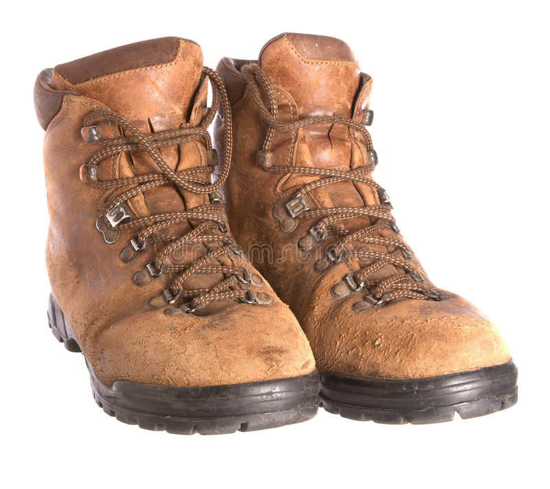 Pair of old worn walking boots. A pair of old worn walking boots isolated on a white background royalty free stock image