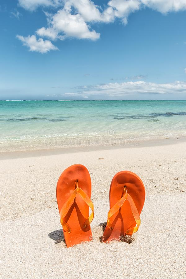 Pair of orange flip-flops in the sand of a tropical beach royalty free stock photos