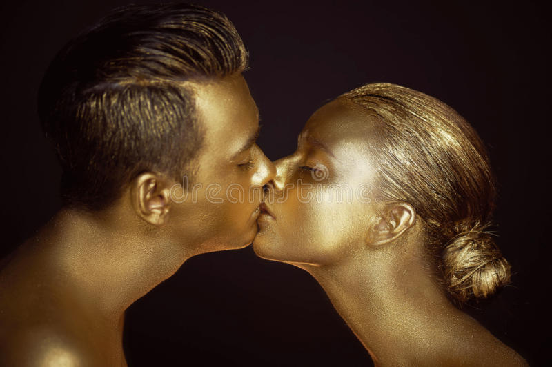 Pair, painted with gold paint, kisses. Affinity, unreality, single unit stock image