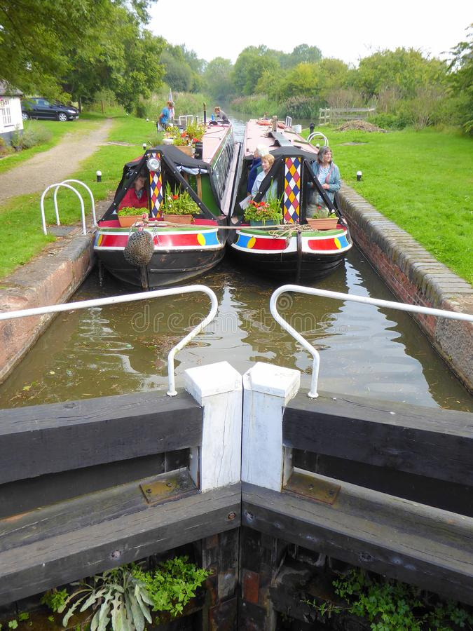 Two narrowboats in a canal lock. A pair of painted narrowboats in a lock side by side on the Droitwich Canal in Worcestershire, England stock images
