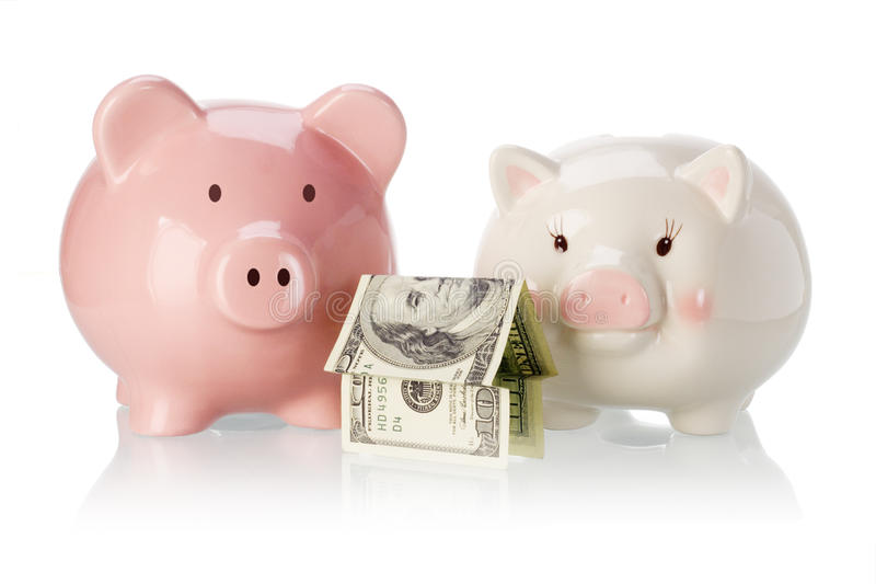 Pair of piggy banks with money house stock photo