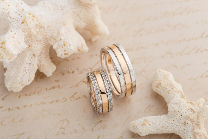 Pair of pink gold and white gold wedding ring with diamonds on f. Emale ring. Two tone silver and gold wedding fashion jewelry. Product concept for jeweler stock photos
