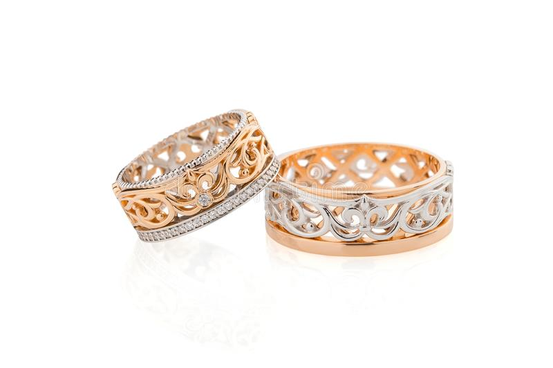 Pair of pink gold and white gold wedding ring with fleur de lis royalty free stock images