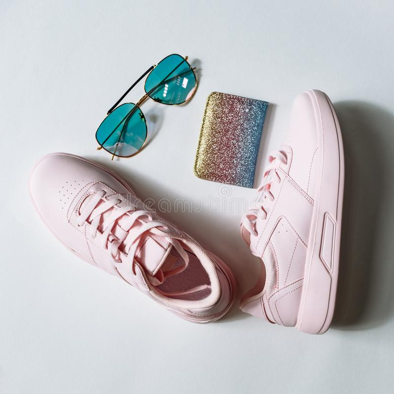 A pair of pink leather sneakers, a purse with multi-colored sequins and sunglasses with blue glass on a white background stock photography
