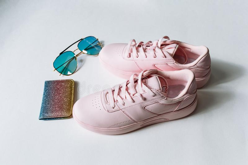 A pair of pink leather sneakers, a purse with multi-colored sequins and sunglasses with blue glass on a white background royalty free stock image