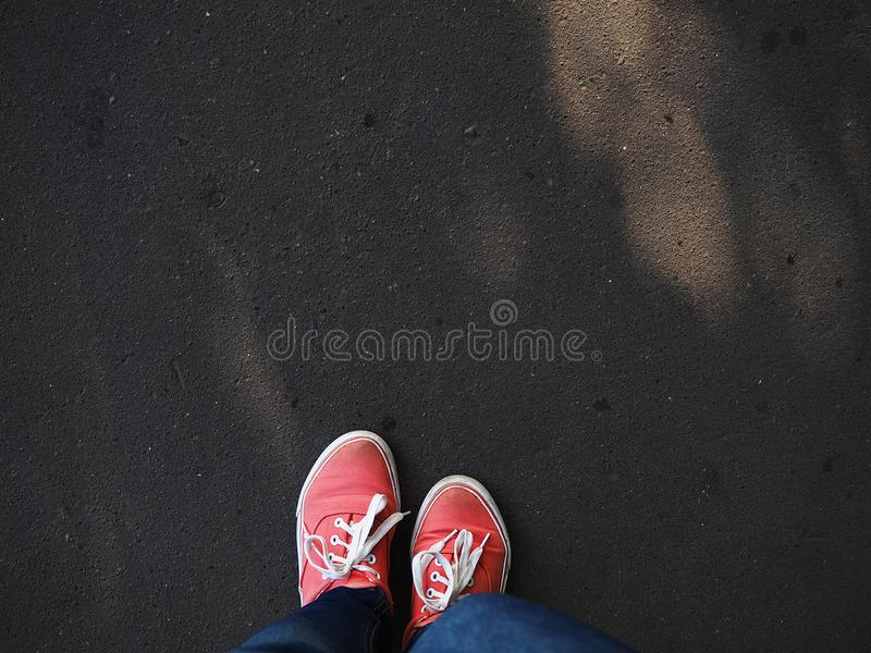 a pair of pink sneakers on the wet asphalt royalty free stock photo