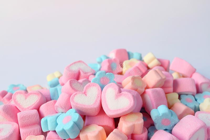 Pair of Pink and White Heart Shaped Marshmallow on the Pile of Pastel Color Flower Shaped Marshmallow Candies with Free Space royalty free stock photo