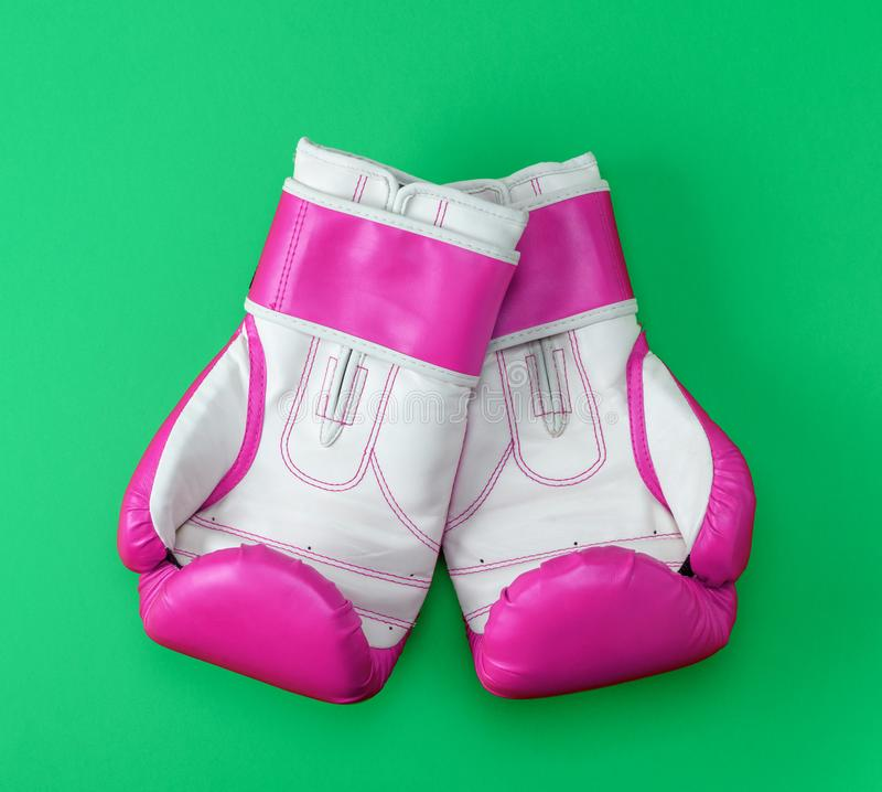 Pair of pink-white leather boxing gloves on a green background. Top view royalty free stock image