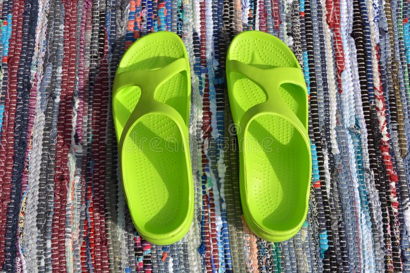 Pair plastic green sandals on handmade carpet background. Pair plastic green sandals on handmade craft carpet background stock image