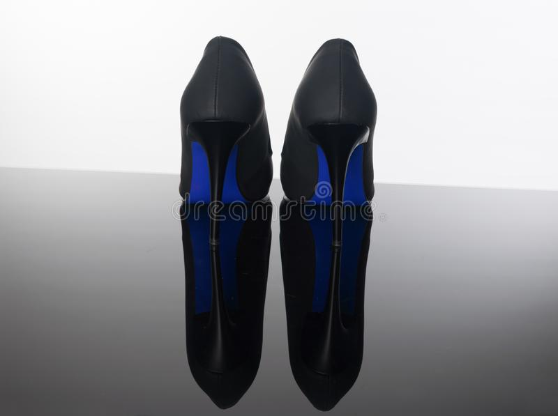 Pair of pointed woman shoes with black soles blue high heels royalty free stock photography