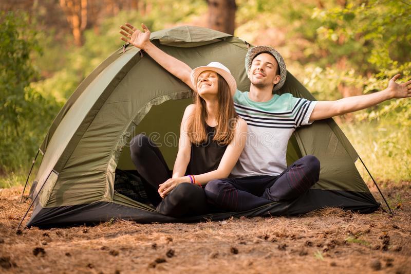 Pair raised their hands up to sunlight on green forest near tent. Concept of active vacation. In camping stock photo