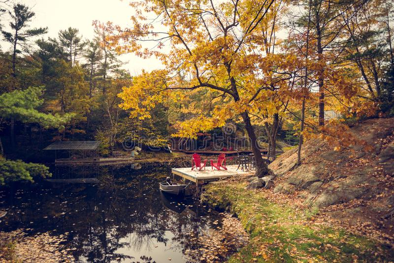 A pair of red chairs on a cottage dock stock photography