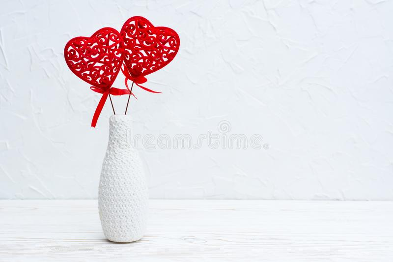 A pair of red curly hearts in a white vase decorated by knitting on the table stock image