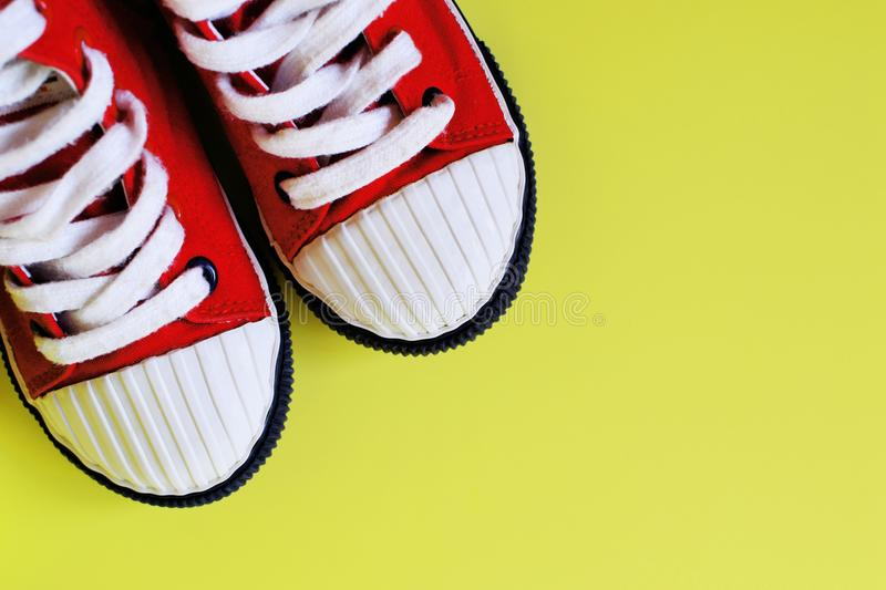 Pair of red kid fabric sneakers on yellow royalty free stock photos