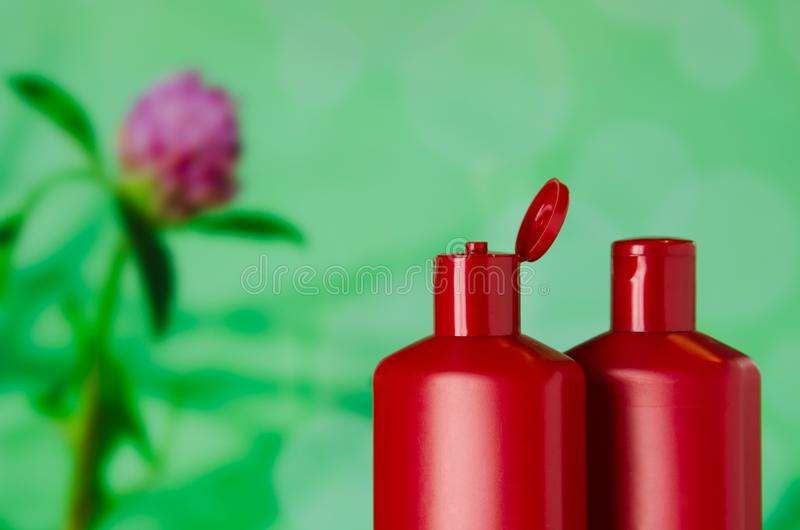 Pair of red plastic bottles from under a cosmetic product on a green background with an blurred image of clover royalty free stock photo