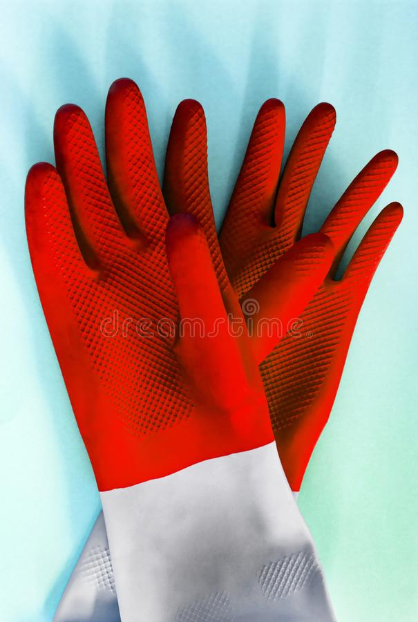 Pair Red rubber gloves for cleaning on blue background, with shadow, top view. housework concept. General or regular cleanup. royalty free stock photos