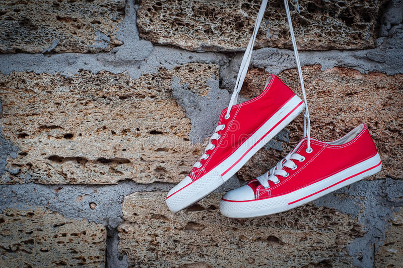 Pair of red sneakers sport on the background wall with brickwork. Empty space royalty free stock images